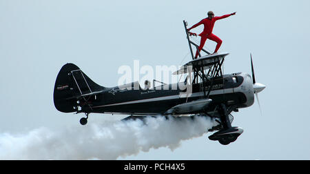 N.C. (Apr. 16, 2005) Р Kyle Franklin strikes a pose during his wing walking routine on the top wing of a jet-powered Waco bi-plane, flown by his father, Jimmy Franklin, during the 2005 Coastal Carolina Air Show in Wilmington, N.C. The 1940 Waco bi-plane is fitted with a T-38 Talon J-85 jet engine along with the 450 horsepower Pratt & Whitney radial prop engine. With both engines turning the Jet Waco puts out over 4,500 pounds of thrust at over 2,000 horsepower. This year's air show showcased civilian and military aircraft from the Nation's armed forces, which provided many flight demonstration - Stock Photo