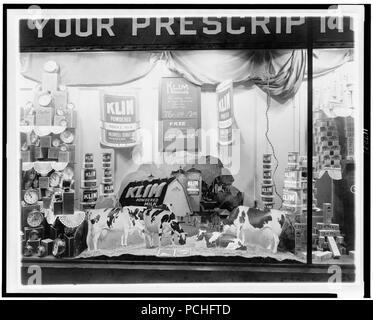 Alarm clocks, powdered milk, and toothpaste in a drug store display window, Washington, D.C. - Stock Photo