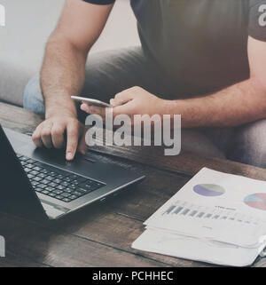 Man works laptop and smartphone on the sofa at home. Work at home concept - Stock Photo