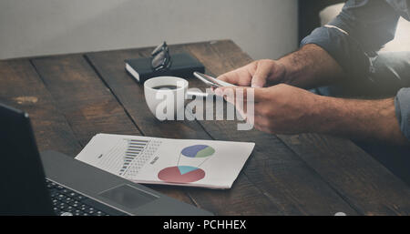 Businessman analyzes the sales report. Analysis of sales and revenue concept - Stock Photo