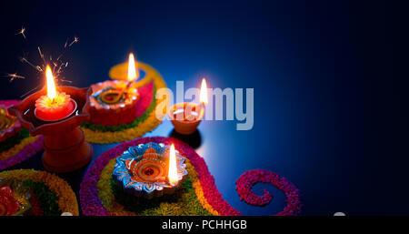 Oil lamps lit on colorful rangoli during diwali celebration - Stock Photo