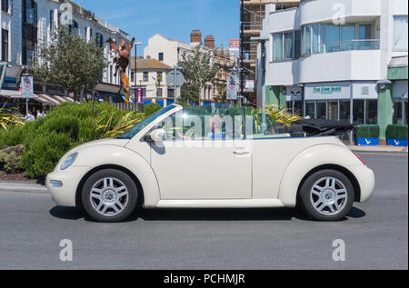 Beige convertible Volkswagen Beetle Cabriolet car from 2005, with the top down, on a road in Summer in West Sussex, England, UK. - Stock Photo
