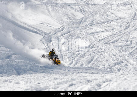 Racer snowmobile on a snowy mountainside. State Nature Reserve in Adygea, Russia, February 2, 2012. - Stock Photo