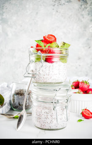 Healthy dietary vegan breakfast, yoghurt with chia seeds and fresh fruits, strawberries, kiwi.White marble background copy space - Stock Photo