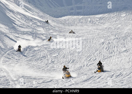 Men driving snowmobiles on snow covered mountainside tracks. State Nature Reserve in Adygea, Russia, February 2, 2012. - Stock Photo
