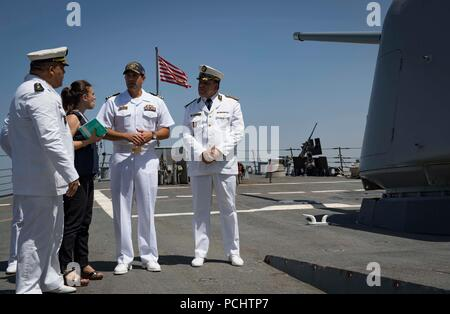 180728-N-UY653-357  ALGIERS, Algeria (July 29, 2018) Cmdr. Tyson Young, center, commanding officer of the Arleigh Burke-class guided-missile destroyer USS Carney (DDG 64), provides a tour of the ship to Algerian Gen. Sameh Zine-Eddine, commander of Central Maritime Zone, 1st Military Region, during the ship's visit to Algiers, Algeria, July 29, 2018. Carney, forward-deployed to Rota, Spain, is on its fifth patrol in the U.S. 6th Fleet area of operations in support of regional allies and partners as well as U.S. national security interests in Europe and Africa. (U.S. Navy photo by Mass Communic - Stock Photo