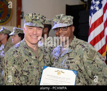 CAMP LEMONNIER, Djibouti – Capt. Charles J. DeGilio, commanding officer of Camp Lemonnier, recognized forward-deployed service members for their dedicated service during the monthly All Hands Ceremony held on base, July 27, 2018. Recipients received the Navy and Marine Corps Achievement Medal and the Navy and Marine Corps Commendation Medal. Congratulations to all the awardees. (U.S. Navy photo by Mass Communication Specialist 1st Class Joe Rullo) - Stock Photo
