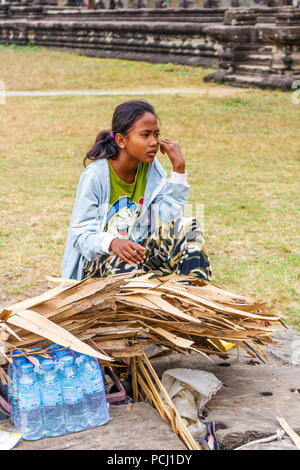 Angkor Wat, Cambodia - 11th January 2018: Woman vendor selling bottles of water. There are many vendors around the complex. - Stock Photo