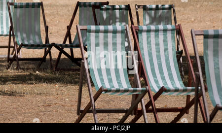 Deck chairs with green and white stripes on dead grass in a parched Hyde Park, London during the heatwave, July 2018. - Stock Photo
