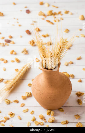 Dry Breakfast of oat flakes, granules and nuts. Muesli on a light table and dry ears in a clay vase - Stock Photo