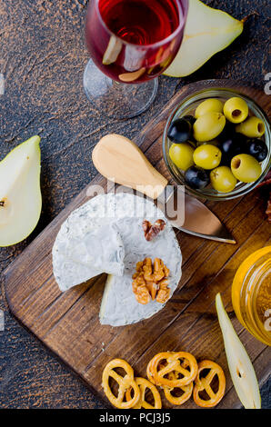 cheese sliced, cheese with mildew, hard cheese, olives, walnuts, peanuts, honey, a glass of wine, a romantic dinner, a meal for the shurman - Stock Photo