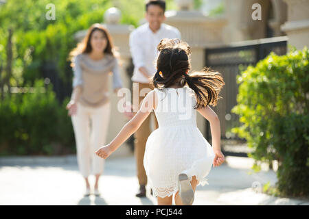 Happy little Chinese girl running towards her parents - Stock Photo