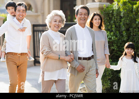 Happy Chinese family strolling outside - Stock Photo