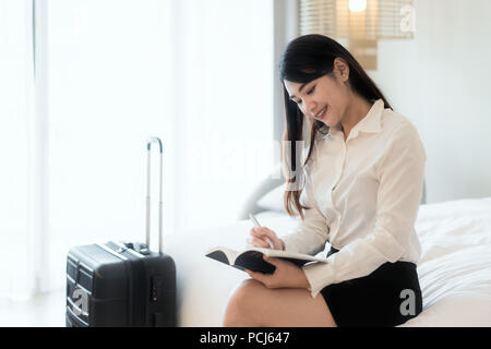 Close up of a happy beautiful Asian business woman smiling cheerfully resting at her hotel suite during business trip making notes and thinking strate - Stock Photo