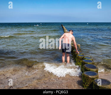 Germany Loddin,Stubbenfelde Beach. Coastal bathing resort on the island of Usedom on the Baltic Sea. Senior elderly man cools off in sea - Stock Photo