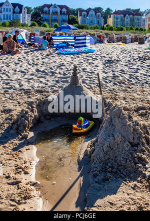 Toy boat & sand castle on crowded Bansin beach as people holiday at the Baltic sea resort on Usedom Island during 2018 Summer heat wave, Heringsdorf,  - Stock Photo
