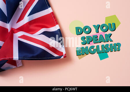 a flag of the United Kingdom and the question do you speak English? on a salmon pink background - Stock Photo