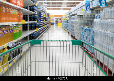 Abstract blurred photo of store with trolley in department store bokeh background. Supermarket aisle with empty green shopping cart - Stock Photo