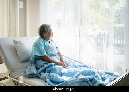 Asian depressed elderly woman patients lying on bed looking out the window in hospital. Elderly woman patients is glad recovered from the illness. - Stock Photo