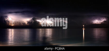 Multiple forks of lightning during a thunderstorm over the ocean. Panoramic with lone boat lit up at night - Stock Photo