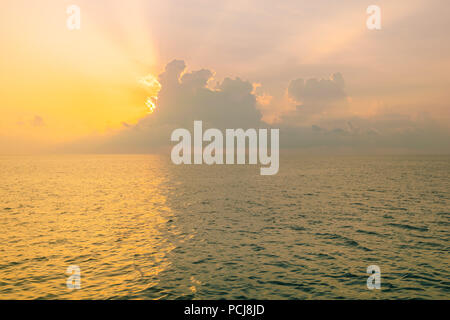 The sun is rising being storm clouds and filtering through, over the Andaman sea in Thailand. - Stock Photo
