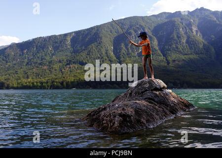 Boy standing on rock fishing in lake - Stock Photo