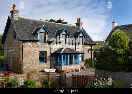 Stone house with blue trim and flower garden on main street of Baile Mor village on Isle of Iona Inner Hebrides Scotland UK - Stock Photo