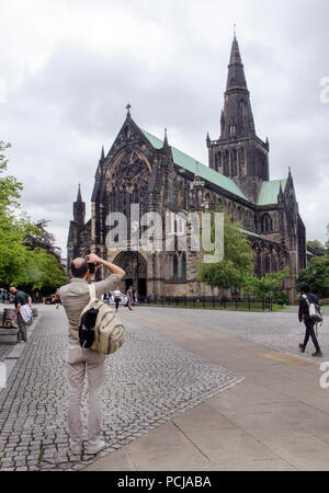 GLASGOW, SCOTLAND - AUGUST 2nd 2018: A tourist taking a photograph of Glasgow Cathedral in the Cathedral Precinct. - Stock Photo