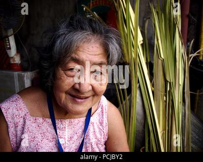 ANTIPOLO CITY, PHILIPPINES - JULY 30, 2018: An elderly Asian woman smiles and pose for the camera. - Stock Photo