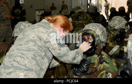 ALPENA, Mich.-- An instructor with the 127th Civil Engineering Squadron assists Tech Sgt. Chanel Daniels, 127th Force Support Squadron, in adjusting her gas mask during Battle Lab training at the Alpena Combat Readiness Training Center on July 29, 2018. During the training, Airmen of the 127th Wing, like Daniels, practiced donning and removing different levels of chemical protection equipment during an operational readiness assessment exercise. (U.S. Air Force photo by Master Sgt. David Kujawa) - Stock Photo