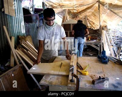 ANTIPOLO CITY, PHILIPPINES - JULY 31, 2018: A carpenter cuts wood using a table saw in his workshop. - Stock Photo