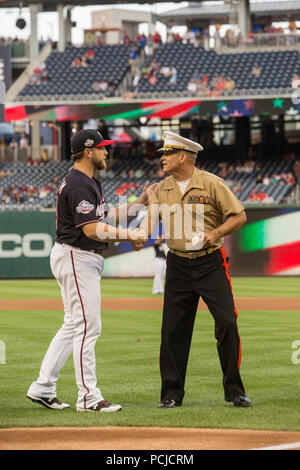 Major Gen. John R. Ewers Jr., staff judge advocate to the Commandant of the Marine Corps, shakes the hand of Washington Nationals catcher, Spencer Kieboom, during U.S. Marine Corps Day at Nationals Park, Washington D.C., July 31, 2018. The Washington Nationals hosted Marines stationed around the National Capital Region to participate in pre-game events to honor the Marine Corps. (Official U.S. Marine Corps photo by Sgt. Robert Knapp/Released) - Stock Photo
