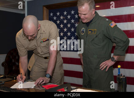 NEWPORT NEWS, Va. (Aug. 1, 2018) Lt. j.g. Zachary Klassen, from Phoenix, assigned to USS Gerald R. Ford's (CVN 78) weapons department, signs his delivery of permanent appointment paperwork during a promotion ceremony aboard Ford. (U.S. Navy photo by Mass Communication Specialist 2nd Class Cat Campbell) - Stock Photo