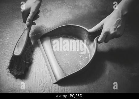 Female Cleaning Dirt On A The Floor With Brush And Dustpan in Monochrome Colors - Stock Photo