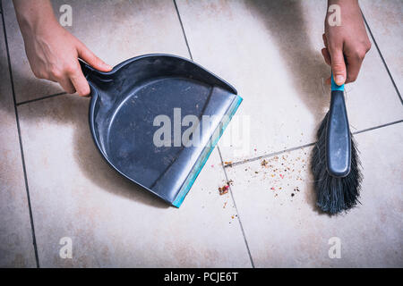 Cleaning Dust On Tile Floor With Brush And Dustpan Holded By Female Hands, High Angle View - Stock Photo