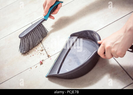 Female Hands Sweeping Dust With A Broom On A Dustpan, Housekeeping Concept - Stock Photo