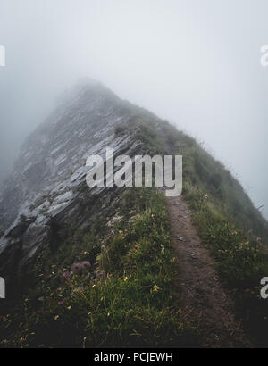 scary hiking path covered in fog on the ridge of a mountain in the swiss alps, brienzer rothorn switzerland vertical - Stock Photo
