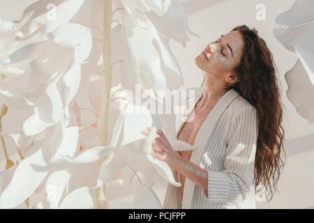 Beautiful woman covered in glitter standing by giant artificial flowers - Stock Photo