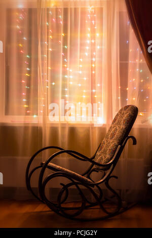 A rocking chair stands by the window in the evening light. - Stock Photo