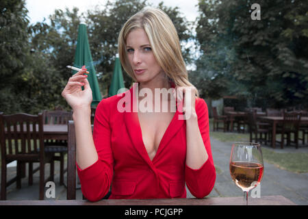 Shoulder length blonde haired woman sitting at a wooden table wearing a low cut red jacket.  She is deep in thought and staring straight ahead. - Stock Photo