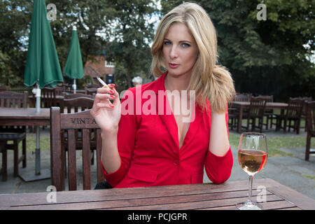 Blonde haired woman sitting at a wooden table wearing a low cut red jacket.  She is holding a cigarette in her hand and a wine glass is on the table. - Stock Photo