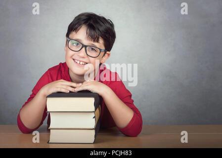 smiling little boy leaning on books on a table on gray background - Stock Photo
