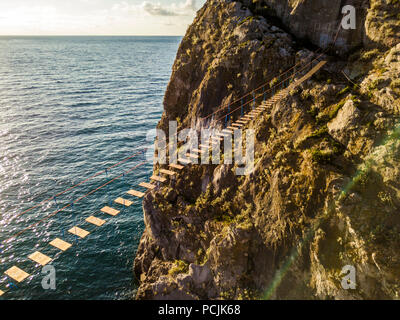 aerial view of rope bridge on a sunset during golden hour mountain near the sea coast - Stock Photo