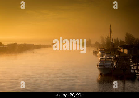 The mouth of the Ausable River in the early morning fog - Stock Photo