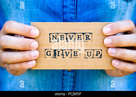 Woman hand holding cardboard card with words Never Give Up made by black alphabet stamps. Denim backgrounds. - Stock Photo