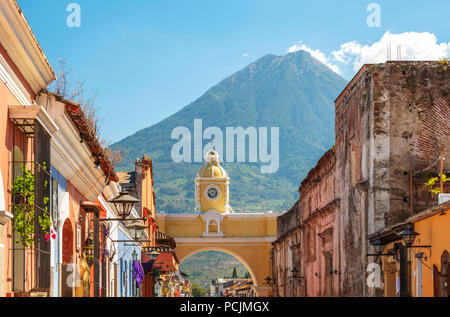 Antigua Guatemala, classic colonial town with famous Arco de Santa Catalina and Volcan de Agua behind - Stock Photo