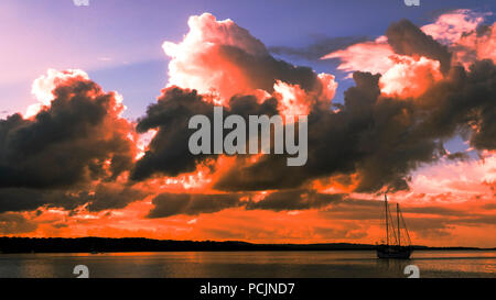 An eye-catching inspirational Orange Red skyscape sunset with predominantly cumulonimbus cloud, in a cerulean blue coloured sky. - Stock Photo
