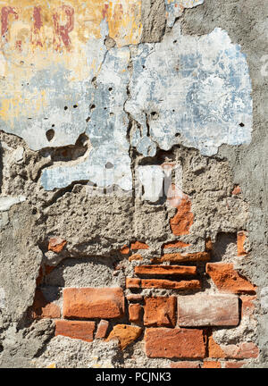 Old damaged brick wall with plaster falling off - Stock Photo