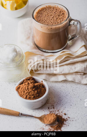 BULLETPROOF CACAO. Ketogenic keto diet hot drink. Cacao blended with coconut oil and butter. Cup of bulletproof cacao and ingredients on white background - Stock Photo