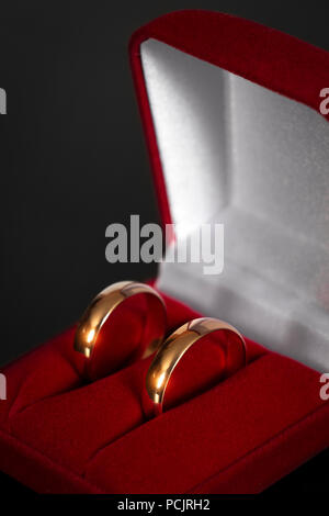 Two wedding rings in a red box on a black background close-up. - Stock Photo